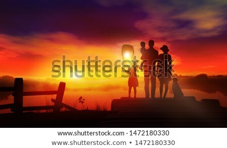Family with children launches a Chinese lantern at sunset Stock photo © ConceptCafe