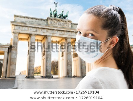 Tourist Woman In Face Mask At Brandenburg Gate Stock photo © AndreyPopov