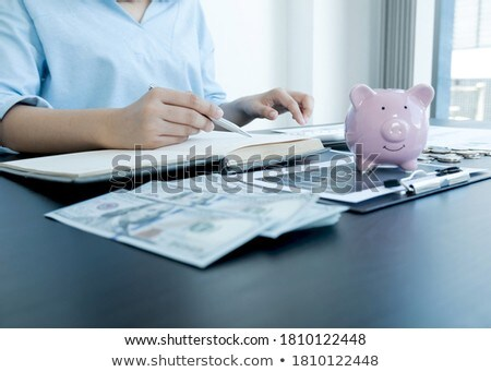 Businessman putting coins into piggy bank and using calculator t Stock photo © Freedomz