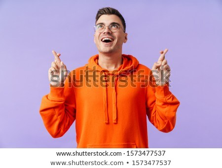 Image of pleased young man posing with fingers crossed Stock photo © deandrobot