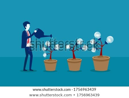 businessman in a suit hold bulb with tree stock photo © cherezoff