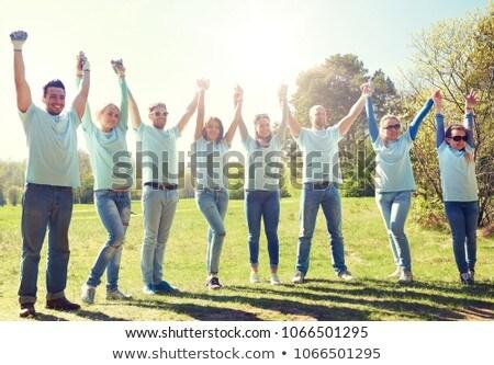 Grupo feliz voluntários de mãos dadas ao ar livre voluntariado Foto stock © dolgachov