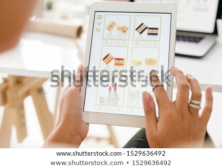 Cosmetic products on touchpad display and human hand scrolling through the stuff Stock photo © pressmaster