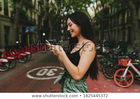 Happy female model with dark long hair calls via cell phone and talks in roaming wears blue jacket l Stock photo © vkstudio