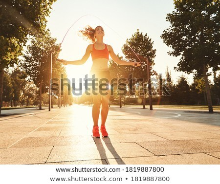 Stock photo: Woman jumping rope outdoors