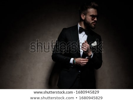 attractive young man wearing a black tuxedo buttons his suit stock photo © feedough