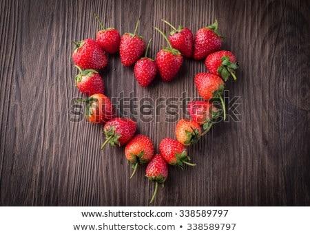 Fresh strawberries array heart shape on old wooden background Stock photo © galitskaya