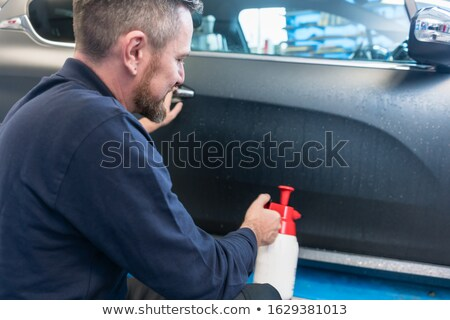 Stockfoto: Man Preparing Car For Putting Advertisement Sticker On It