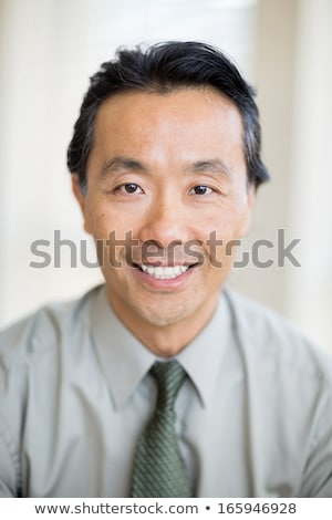 Front view of confident Asian male doctor looking at medical report in clinic at hospital. Colleague Stock photo © wavebreak_media