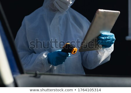 Protected worker wearing cloth, mask and gloves using tablet, co Stock photo © simazoran