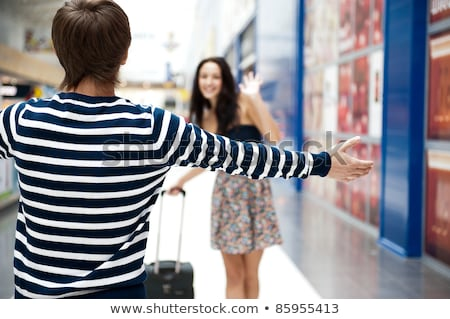 Young man meeting his girlfriend with opened arms at airport arr Stock photo © HASLOO