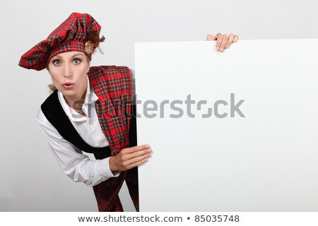 Surprised woman in traditional Scottish outfit with a board left blank for your message Stock photo © photography33