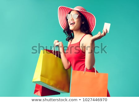 young woman holding shopping bags and credit card stock photo © stockyimages
