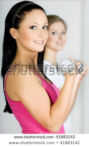 Happy young woman doing dumbbell curl Stock photo © sumners