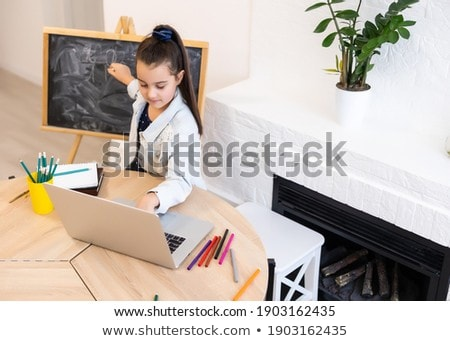 happy little girl drawing on chalk board at home stock photo © dolgachov