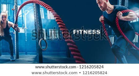 Strong woman exercising with battle ropes during functional training Stock photo © Kzenon