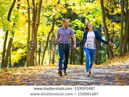 Stock photo: lovers is running with hold hands on city park