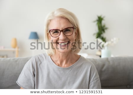 portrait of beautiful middle age mature senior woman posing on a sofa at home Stock photo © Lopolo