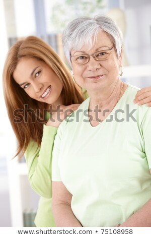mother and attractive young daughter smiling happily, looking at Stock photo © dacasdo