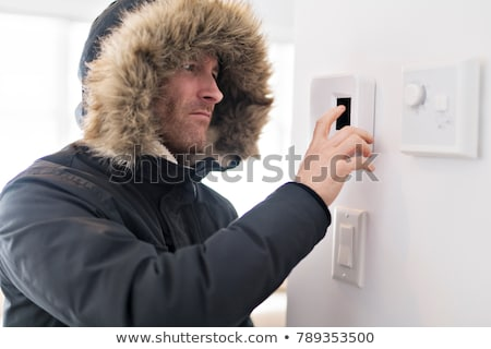 A man set the thermostat at house Stock photo © Lopolo