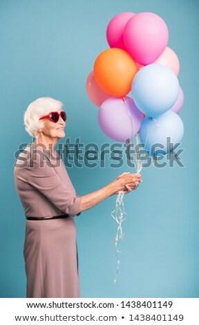 Elegant and gracious senior female holding bunch of balloons Stock photo © pressmaster