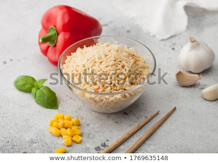 Glass bowl with boiled long grain basmati rice with vegetables on light table background with sticks Stock photo © DenisMArt