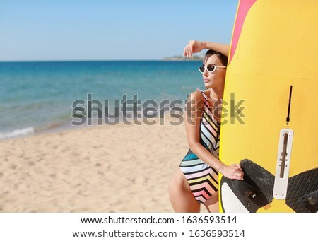 A surf athlete in a sports swimsuit and sunglasses on a sandy beach Stock photo © ElenaBatkova