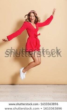 Photo of excited woman in red dress listening to music with head Stock photo © deandrobot