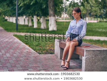 Young woman with sunglasses sitting in the park and daydreaming Stock photo © boggy