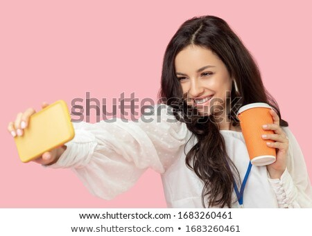 Photo of pretty pleased woman in earrings smiling with fingers crossed Stock photo © deandrobot