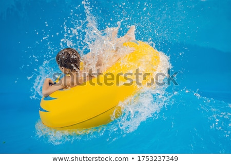 Boy on a pool float on artificial waves in a water park Stock photo © galitskaya