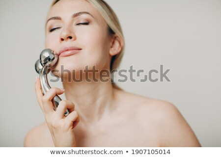 Beauty girl holding drainage massage face roller Stock photo © DenisMArt