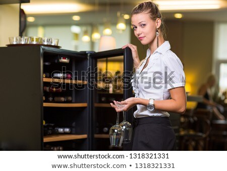 Cute waitress getting a bottle of a nice wine for the guests  Stock photo © lightpoet
