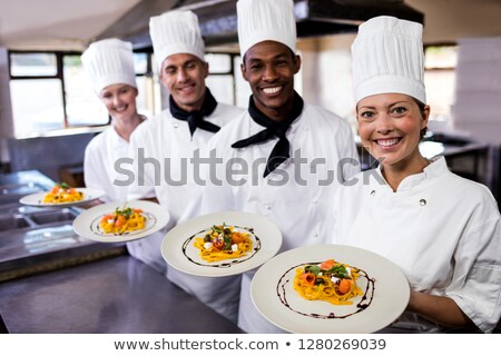 Group of chefs holding plate of prepared pasta in kitchen at hotel Stock photo © wavebreak_media
