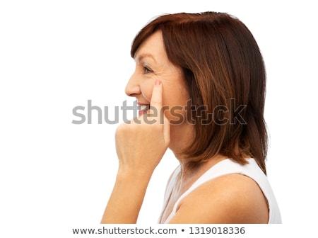 profile of senior woman pointing to eye wrinkles Stock photo © dolgachov