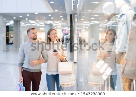 Pretty female with drink and paperbags and her husband passing by shopwindow Stock photo © pressmaster