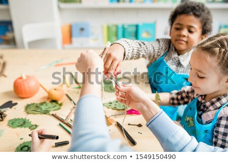 Cute schoolboy cutting thread with scissors while helping his teacher at lesson Stock photo © pressmaster