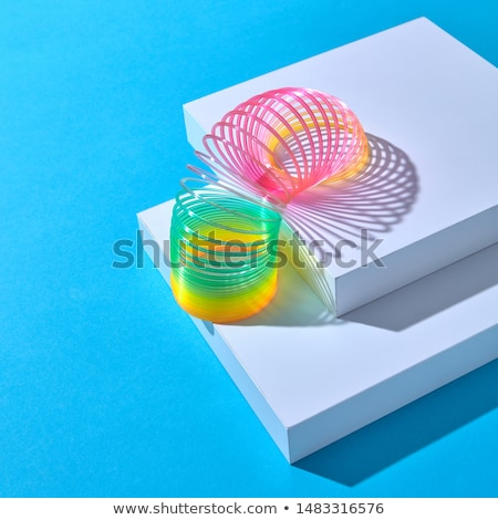 Vertical stretching plastic slinky toy with curved shadow. Stock photo © artjazz