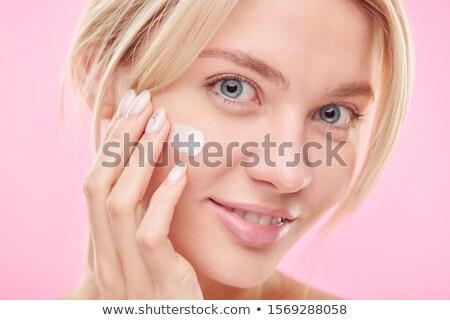 Attractive female applying hydrating cream on cheek during skincare procedure Stock photo © pressmaster
