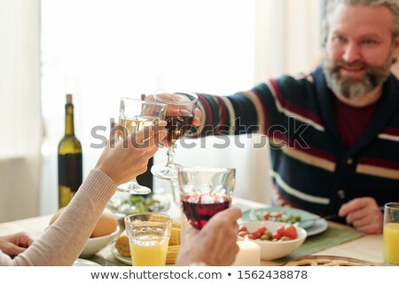 Mature man and his daughter clinking with glasses of wine over snacks on table Stock photo © pressmaster