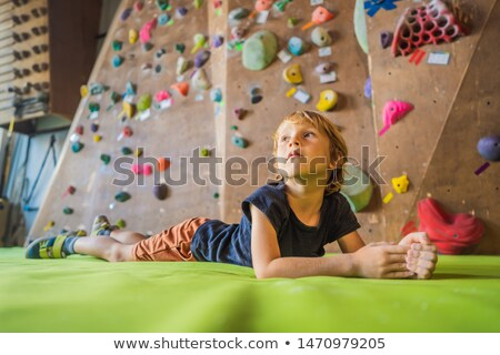 Boy resting after climbing a rock wall indoor Stock photo © galitskaya