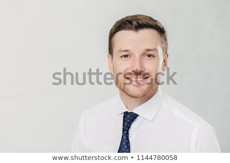 Headshot of attractive unshaven young male with cheerful expression, looks confidently at camera, be Stock photo © vkstudio