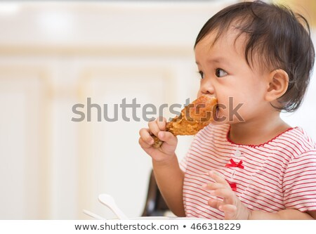 Cute girl eating fried chicken on white background Stock photo © bluering