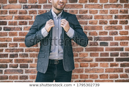 Suit man smart casual outfit young businessman adjusting collar of his blue wool blazer with shirt a Stock photo © Maridav