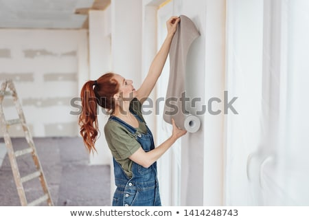 young woman tries on wall-papers to wall Stock photo © Paha_L