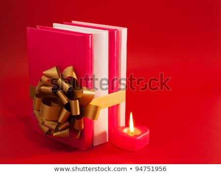 row of books tied up with ribbon and burning candle stock photo © andreykr