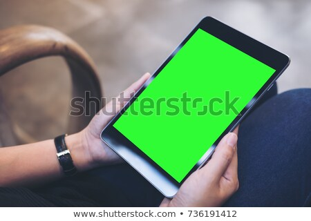 Young woman holding fingers crossed over green screen background Stock photo © rosipro