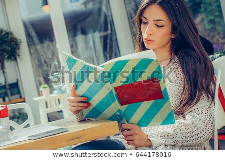 young woman reading menu in a cafe indoors stock photo © hasloo