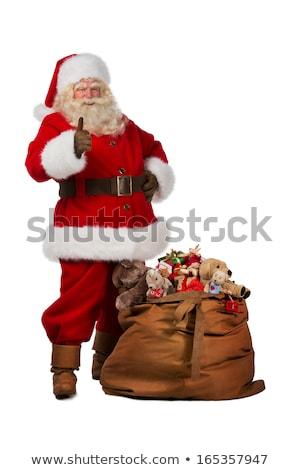 santa claus posing near a bag full of gifts and thumbs up stock photo © hasloo
