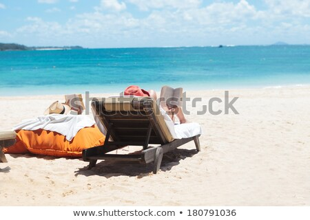 couple of people reading while sunbathing on the beach stock photo © feedough